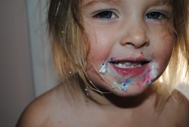 A two-year-old enjoys some homemade cupcakes with frosting and sprinkles in 2013.
